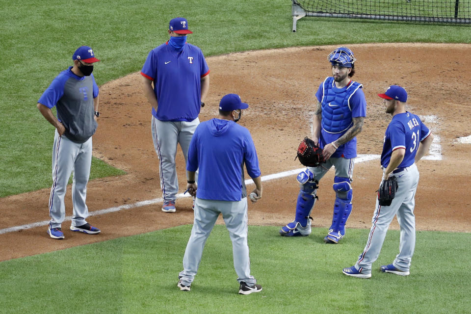 Texas Rangers manager Chris Woodward, left, bullpen coach Doug Mathis, second from left, pitching coach Julio Rangel, center front, catcher Blake Swihart, second from right, and pitcher Cody Allen, right, talk after Allen threw in a baseball practice at Globe Life Field in Arlington, Texas, Friday, July 3, 2020. (AP Photo/Tony Gutierrez)