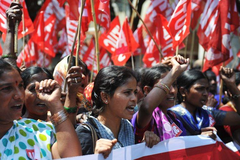 """Indian workers rally during a two-day strike called by trade unions opposing the government's economic policies in Hyderabad on February 20, 2013. Millions of India's workers walked off their jobs on Wednesday in a two-day nationwide strike called by trade unions to protest at the """"anti-labour"""" policies of the embattled government"""
