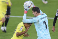 Real Madrid's goalkeeper Thibaut Courtois deserves the ball ahead of Villareal's Carlos Bacca during the Spanish La Liga soccer match between Villarreal and Real Madrid in Ceramica stadium in Villarreal, Spain, Saturday Nov. 21, 2020. (AP Photo/Alberto Saiz)