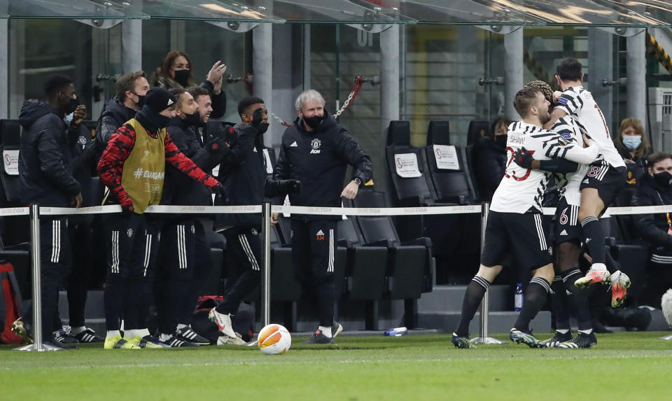 Manchester United's Paul Pogba, second right, celebrates with teammates after scoring his team's first goal during the Europa League round of 16 second leg soccer match between AC Milan and Manchester United at the San Siro Stadium, in Milan, Italy, Thursday, March 18, 2021. (AP Photo/Antonio Calanni)
