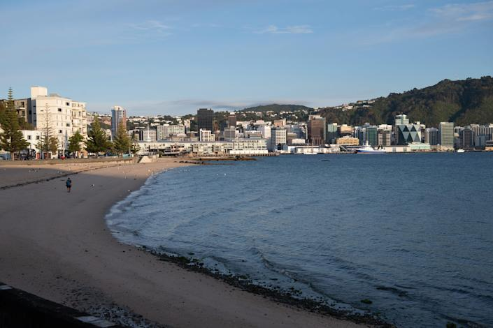 One man walks along a New Zealand beach with a small coastal town in the background