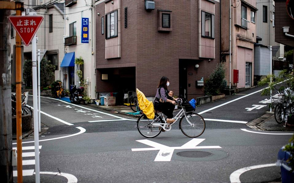 A masked woman cycles across junction with a small child between her legs - Behrouz Mehri/AFP