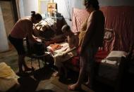 Cerebrovascular accident (CVA) patient Pedro, sits on his bed before being washed with the help of his daughter Daniela (L), 38, and wife Maria Do Carmo, 70, inside their house in Brasilandia slum, of which they are without water for 13 hours a day, in Sao Paulo February 11, 2015. REUTERS/Nacho Doce