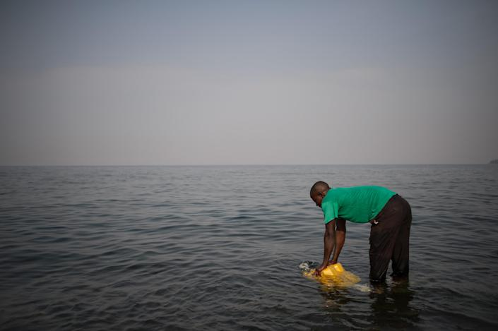 A man fills a jerrycan with water from Lake Kivu on the Himbi beach in Goma, in the east of the Democratic Republic of Congo on August 11, 2013 (AFP Photo/Phil Moore)