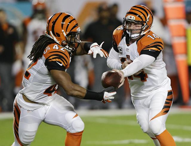 Cincinnati Bengals quarterback Andy Dalton (14) hands the ball to running back BenJarvus Green-Ellis during the first half of an NFL football game against the Miami Dolphins, Thursday, Oct. 31, 2013, in Miami Gardens, Fla. (AP Photo/Wilfredo Lee)