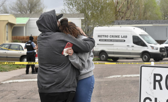 Freddy Marquez kisses the head of his wife, Nubia Marquez, near the scene where her mother and other family members were killed in a mass shooting early Sunday, May 9, 2021, in Colorado Springs, Colo. The suspected shooter was the boyfriend of a female victim at the party attended by friends, family and children. He walked inside and opened fire before shooting himself, police said. Children at the attack weren't hurt and were placed with relatives. (Jerilee Bennett/The Gazette via AP)