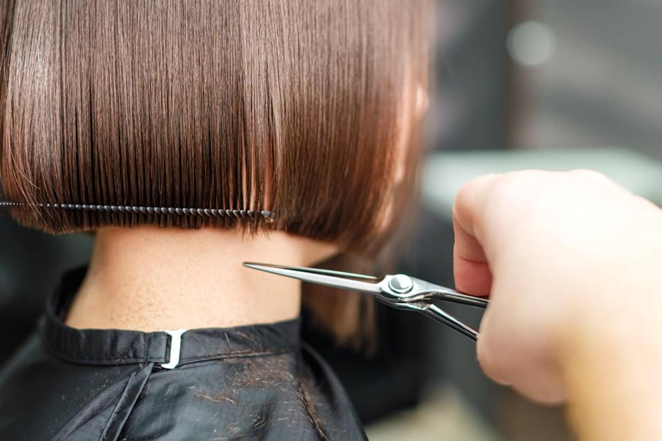 Hairdresser's hands are cutting brown short hair with scissors close up.