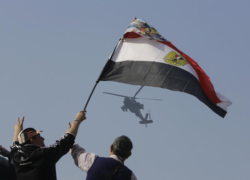 Egyptians wave a national flag as they greet an army helicopter flying over Tahrir Square, the epicenter of the 2011 uprising, in Cairo, Egypt, Saturday, Jan. 25, 2014. As Egyptians mark the third anniversary of their spectacular revolt against autocrat Hosni Mubarak in the name of democracy on Saturday, there has been a powerful sign of the country's stunning reversals since: letters of despair by some of the prominent activists who helped lead the uprising, leaked from the prisons where they are now jailed. (AP Photo/Amr Nabil)