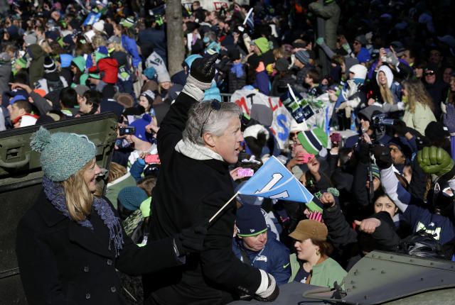 Seattle Seahawks head coach Pete Carroll, center, waves with his wife Glena during the Super Bowl champions parade on Wednesday, Feb. 5, 2014, in Seattle. The Seahawks defeated the Denver Broncos 43-8 in NFL football's Super Bowl XLVIII on Sunday. (AP Photo/Ted S. Warren)