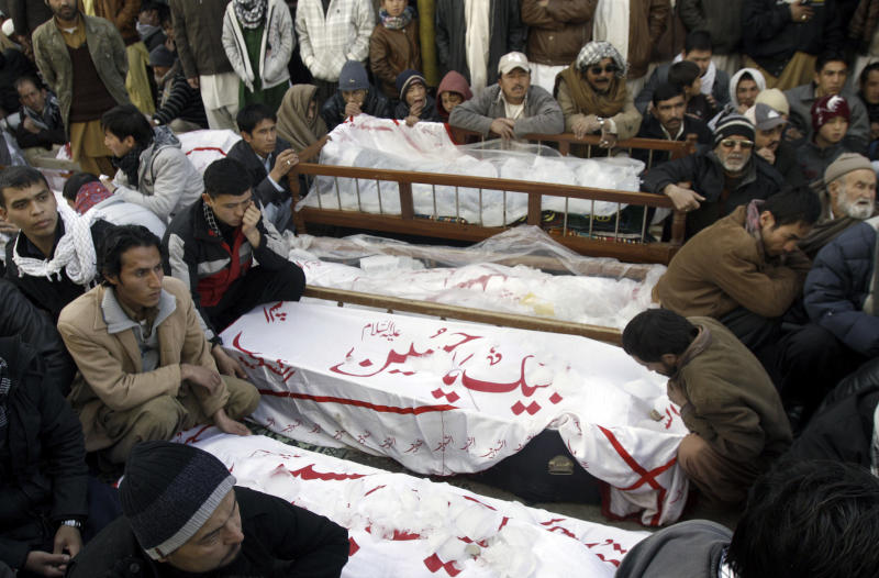 """FILE - On this Saturday, Jan. 12, 2013 file photo, Pakistani Shiite Muslims sit next to the bodies of their relatives awaiting burial, who were killed in Thursday's deadly bombings, during a protest in Quetta, Pakistan. Pakistan's minority Shiite Muslims have started using the word """"genocide"""" to describe a spike in attacks against them by Sunni militants with suspected links to the country's security agencies and a mainstream political party. The violence, which has killed nearly 300 Shiites this year alone, has thrown a spotlight on the freedoms politicians here give extremist groups and the murky and protracted relationship between militants and the nation's military and intelligence services. (AP Photo/Arshad Butt, File)"""