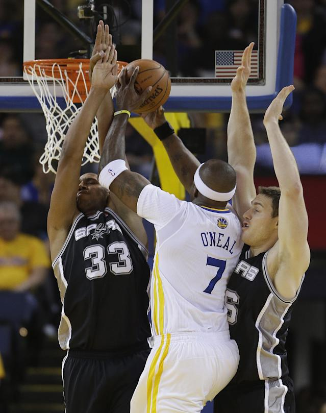 Golden State Warriors center Jermaine O'Neal goes to the basket against San Antonio Spurs forwards Boris Diaw, left, and Aron Baynes, right, during the first quarter of their NBA basketball game Saturday, March 22, 2014, in Oakland, Calif. (AP Photo/Eric Risberg)