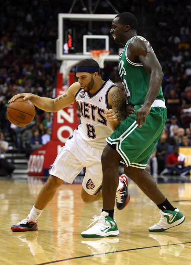 NEWARK, NJ - APRIL 14: Deron Williams #8 of the New Jersey Nets drives in the secon dhalf against Brandon Bass #30 of the Boston Celtics at Prudential Center on April 14, 2012 in Newark, New Jersey. NOTE TO USER: User expressly acknowledges and agrees that, by downloading and or using this photograph, User is consenting to the terms and conditions of the Getty Images License Agreement. (Photo by Chris Chambers/Getty Images)