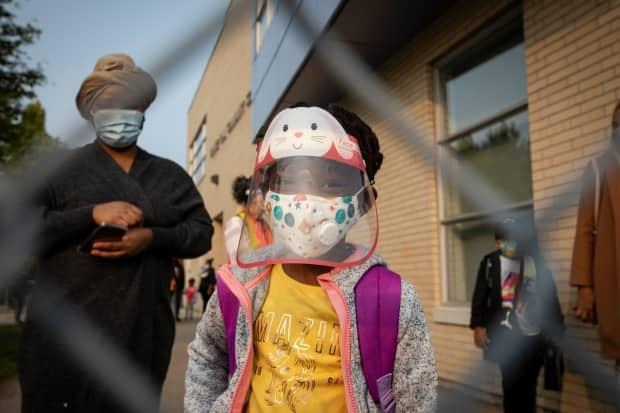 A Toronto elementary school student wears full PPE before heading into class last September. Students will continue to wear masks inside classrooms as part of Ontario's new plan. (Evan Mitsui/CBC - image credit)