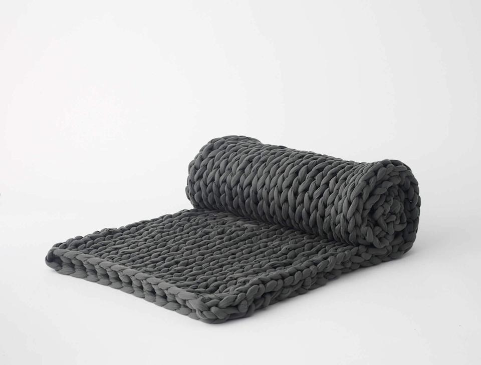 """<h3><a href=""""https://bearaby.com/products/the-napper"""" rel=""""nofollow noopener"""" target=""""_blank"""" data-ylk=""""slk:Bearaby Blanket"""" class=""""link rapid-noclick-resp"""">Bearaby Blanket </a> </h3><br><br>I was very skeptical when I first received this blanket, mostly because it was heavy AF. My 20 pound napper came in a large cloth bag — the kind you'd usually use to tote laundry — and when I first picked it up, I thought it was surely full of tiny dumbbells. It stressed me out just thinking about carrying it all the way to my bed.<br><br>However, once I unfolded it, and thrust it up over my legs and torso, it felt like a weight was lifted from my shoulders and transformed into a magical cloak of relief. It was a weird sensation, but I felt like my Cortisol (the primary stress hormone) levels were plummeting, and I was ready to relax.<br><br>Some research has shown that sleeping under evenly dispersed weight can help deepen sleep cycles and lower anxiety and stress levels. Blankets like these mimic the sensation of being swaddled or hugged, and use Deep Touch Pressure which is said to stimulate the production of serotonin, a <a href=""""https://www.livescience.com/59315-weighted-blankets-faq.html"""" rel=""""nofollow noopener"""" target=""""_blank"""" data-ylk=""""slk:neurotransmitter that helps us feel calm"""" class=""""link rapid-noclick-resp"""">neurotransmitter that helps us feel calm</a>. If none of that works for you, know that Bearaby is a super environmentally friendly company, so buying these woven blankets is good for the planet.<br><br>For the record, when I first got my blanket, it smelled a little like a warehouse. However, that's nothing that a few squirts of This Works Pillow Spray didn't fix.<br><br><strong>Bearaby</strong> The Napper, $, available at <a href=""""https://go.skimresources.com/?id=30283X879131&url=https%3A%2F%2Fbearaby.com%2Fproducts%2Fthe-napper"""" rel=""""nofollow noopener"""" target=""""_blank"""" data-ylk=""""slk:Bearaby"""" class=""""link rapid-noclick-resp"""">Bearaby</a>"""