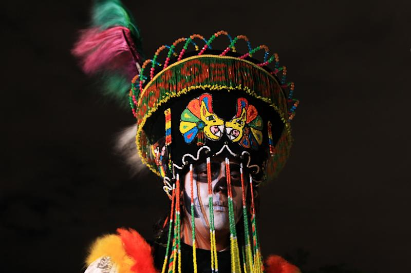 "Faithful Luis Castillo dressed as a traditional Mexican ""Catrina"" poses during Day of the Dead celebrations at Mexico's National Autonomous University in Mexico City, Wednesday, Oct. 30, 2013. Known as the ""Catrina,"" the figure of a skeleton wearing an elegant broad-brimmed hat was first done as a satirical engraving by artist Jose Guadalupe Posada somewhere between 1910 and his death on Jan. 20, 1913. (AP Photo/Marco Ugarte)"