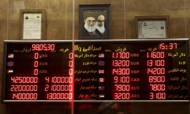Various rates and prices for currencies and gold coins are displayed at an exchange bureau, in Tehran, Iran, Wednesday, Aug. 21, 2019. Iran's president sent a bill to parliament Wednesday that would cut four zeroes from the value of the Islamic Republic's sanctions-battered currency, the rial, as tensions remain high between Tehran and Washington. (AP Photo/Ebrahim Noroozi)
