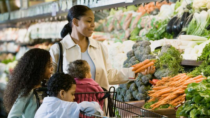 Mother and three kids shopping for produce