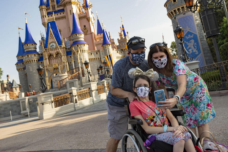 LAKE BUENA VISTA, FL - JULY 11:  In this handout photo provided by Walt Disney World Resort, guests take a selfie at Magic Kingdom Park at Walt Disney World Resort on July 11, 2020 in Lake Buena Vista, Florida. July 11, 2020 is the first day of the phased reopening. (Photo by Matt Stroshane/Walt Disney World Resort via Getty Images)
