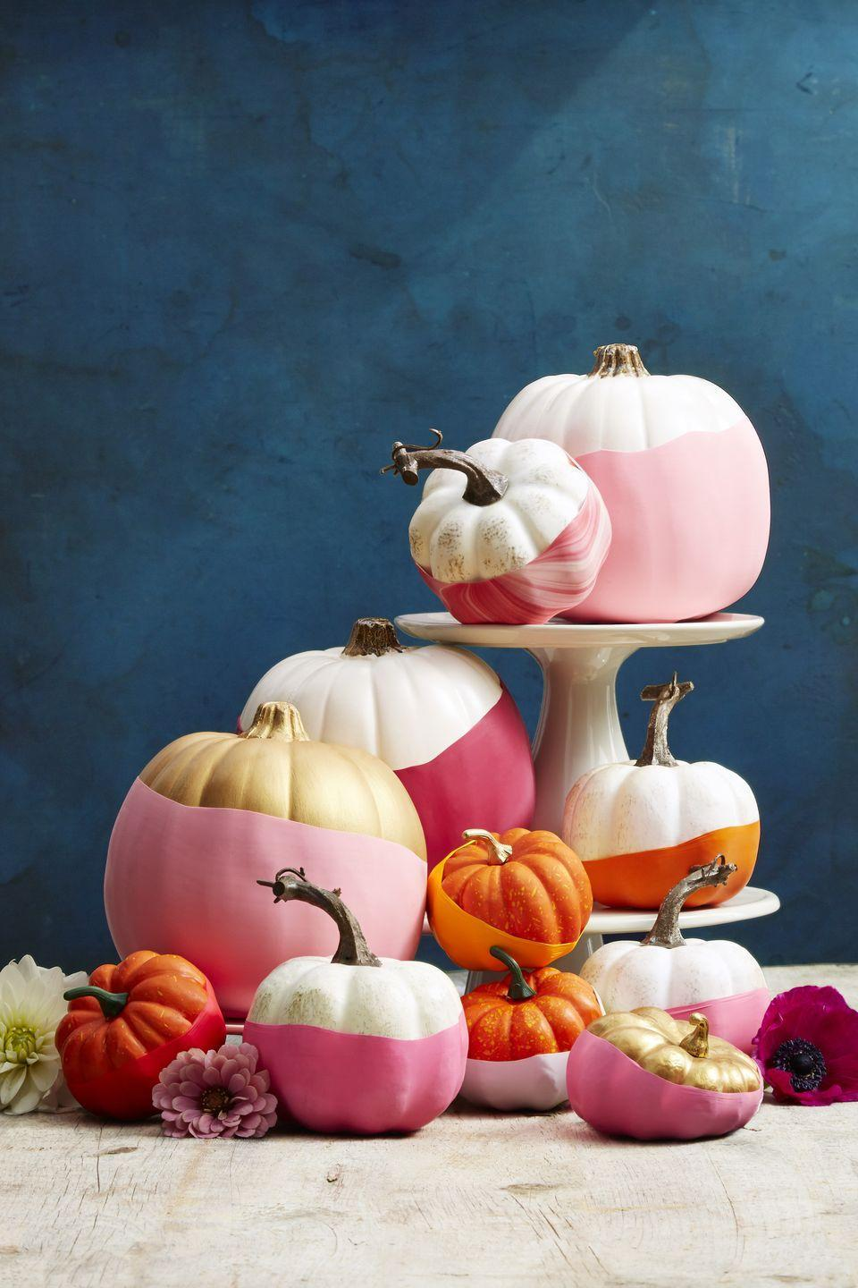 """<p>We spotted this <a href=""""http://www.papernstitchblog.com/2015/10/12/easiest-no-carve-pumpkin-idea-balloon-dipped-pumpkins-diy/"""" rel=""""nofollow noopener"""" target=""""_blank"""" data-ylk=""""slk:&quot;dipped&quot;-looking pumpkin DIY"""" class=""""link rapid-noclick-resp"""">""""dipped""""-looking pumpkin DIY</a> on Brittni Mehlhoff's blog, <a href=""""http://www.papernstitchblog.com/"""" rel=""""nofollow noopener"""" target=""""_blank"""" data-ylk=""""slk:Paper & Stitch"""" class=""""link rapid-noclick-resp"""">Paper & Stitch</a>, and put it on our cover. For a pop of color, snip the ends off opaque balloons (11 inches for mini pumpkins, larger for the big guys) and stretch around the bases. </p><p><a class=""""link rapid-noclick-resp"""" href=""""https://www.amazon.com/Balloons-Assorted-Birthday-Decoration-Accessory/dp/B07MKWX51X/?tag=syn-yahoo-20&ascsubtag=%5Bartid%7C10055.g.1714%5Bsrc%7Cyahoo-us"""" rel=""""nofollow noopener"""" target=""""_blank"""" data-ylk=""""slk:SHOP BALLOONS"""">SHOP BALLOONS</a><br></p>"""