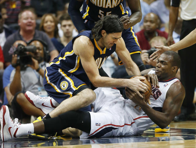 CORRECTS TO THURSDAY NOT WEDNESDAY - Indiana Pacers forward Luis Scola, left, and Atlanta Hawks forward Paul Millsap fight for a loose ball in the first half of Game 3 of an NBA basketball first-round playoff series on Thursday, April 24, 2014, in Atlanta. (AP Photo/John Bazemore)