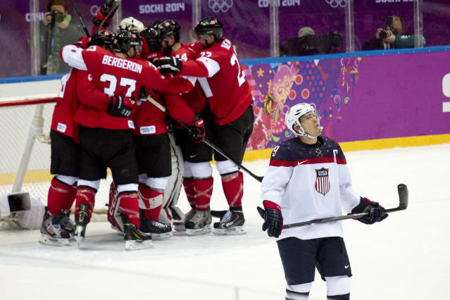 USA forward Zach Parise looks up at the scoreboard as Canada celebrates their 1-0 victory in men's semifinal ice hockey game at the 2014 Winter Olympics, Friday, Feb. 21, 2014, in Sochi, Russia. (AP Photo/J. David Ake)