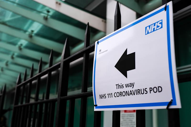 A sign directs patients towards an NHS 111 Coronavirus (COVID-19) Pod, where people who believe they may be suffering from the virus can attend and speak to doctors, at London University Hospital in London on March 5, 2020. (Photo by Alberto Pezzali/NurPhoto via Getty Images)