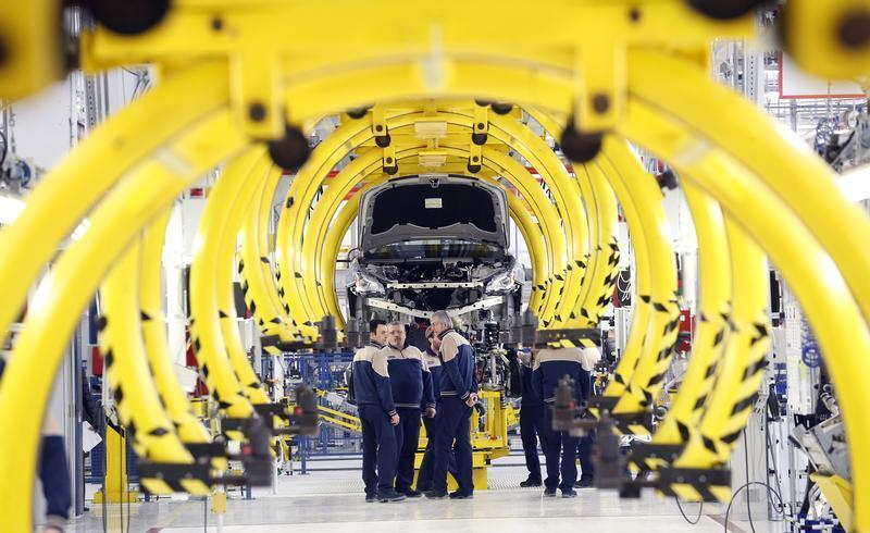 Employees stand in front of a new car at the Maserati new opening plant in Turin