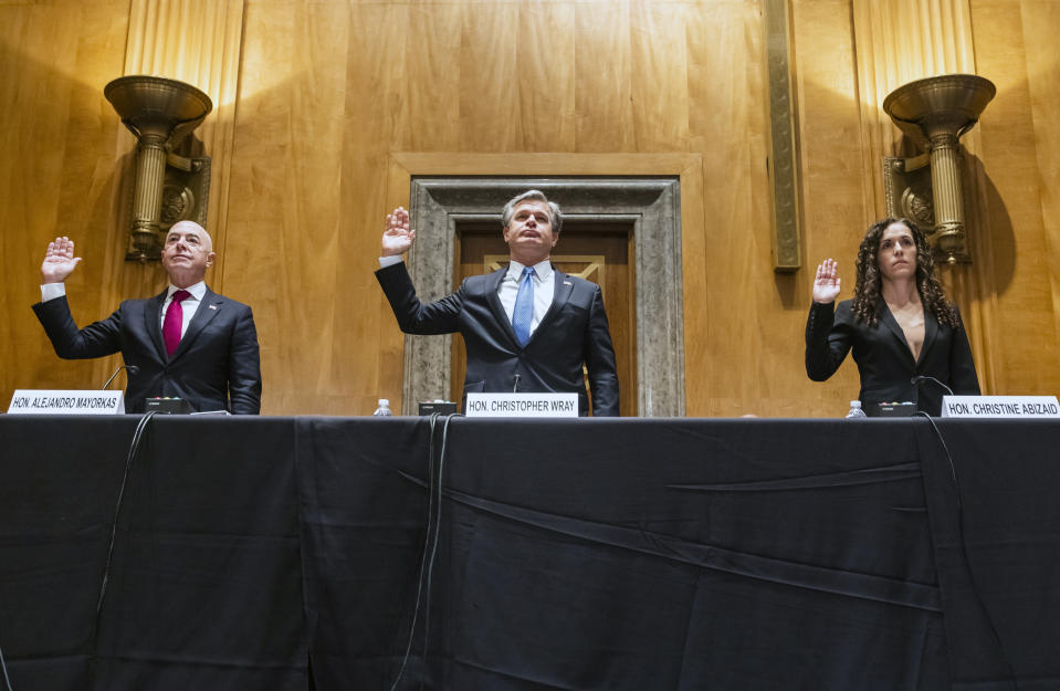 Secretary of Homeland Security Alejandro Mayorkas, left, FBI Director Christopher Wray, center, and Director of the National Counterterrorism Center Christine Abizaid, are sworn-in prior to testifying before a Senate Homeland Security and Governmental Affairs Committee hearing to discuss security threats 20 years after the 9/11 terrorist attacks, Tuesday, Sept. 21, 2021 on Capitol Hill in Washington. (Jim Lo Scalzo/Pool via AP)