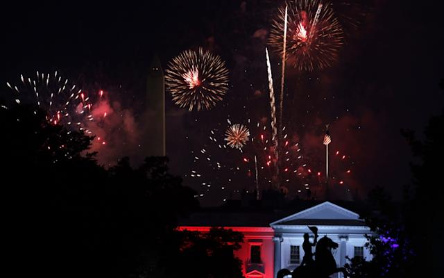 Fireworks explode behind the White House near the Washington Monument on July 4 - Getty