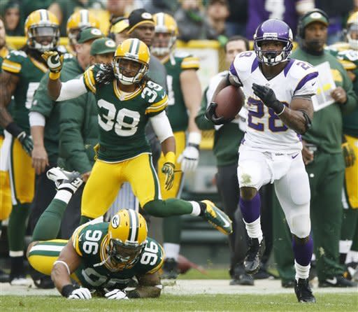 Minnesota Vikings running back Adrian Peterson breaks away from Green Bay Packers' Tramon Williams (38) and Mike Neal (96) for an 82-yard touchdown run during the first half of an NFL football game Sunday, Dec. 2, 2012, in Green Bay, Wis. (AP Photo/Tom Lynn)