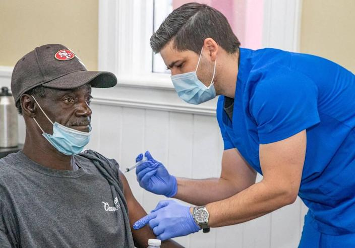 Medical assistant Mauricio Garcia injects Richard Anthony Sanders, a resident at Chapman Partnership, with the Moderna COVID-19 vaccine. Vaccinations were administered to residents, staff and families at the homeless shelter on Thursday, April 22, 2021.