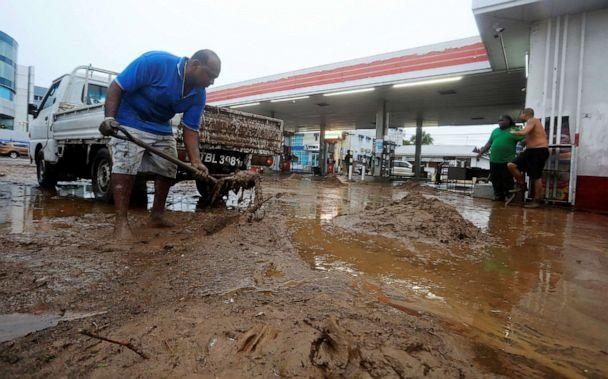 PHOTO: Residents remove mud from a gas station during a rain storm caused by Tropical Storm Karen in Barataria, Trinidad and Tobago, Sept. 22, 2019. (Andrea De Silva/Reuters)