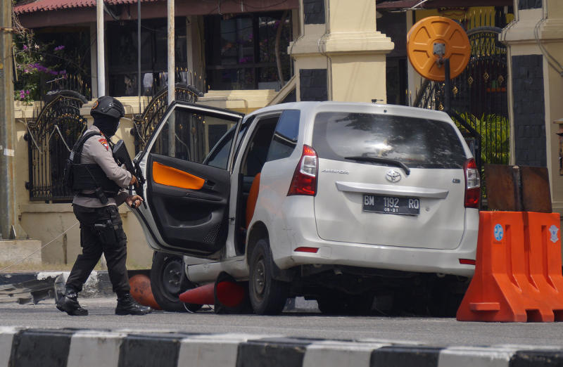An officer inspects a minivan used in the attack at the regional police headquarters in Pekanbaru, Riau province, Indonesia, Wednesday, May 16, 2018. Indonesian police on Wednesday shot dead sword-wielding men who attacked the police headquarters in Sumatra, killing one officer, the latest in a spate of militant attacks across the Muslim-majority country. (AP Photo/Akbari)
