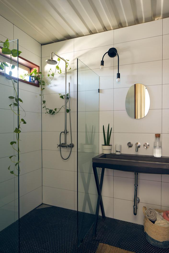 Without a shower curb, the bathroom is a full wet room. The airy, modern space includes classic penny tile on the floor, a custom fabricated sink basin, and a roomy shower. It features an asymmetrical sconce from Schoolhouse Electric.