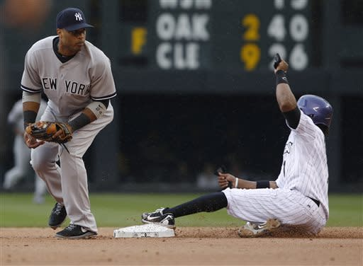 New York Yankees second baseman Robinson Cano, left, forces out Colorado Rockies' Eric Young, Jr., at second base on a ground ball hit by Dexter Fowler in the first inning of a baseball game in Denver on Thursday, May 9, 2013. (AP Photo/David Zalubowski)