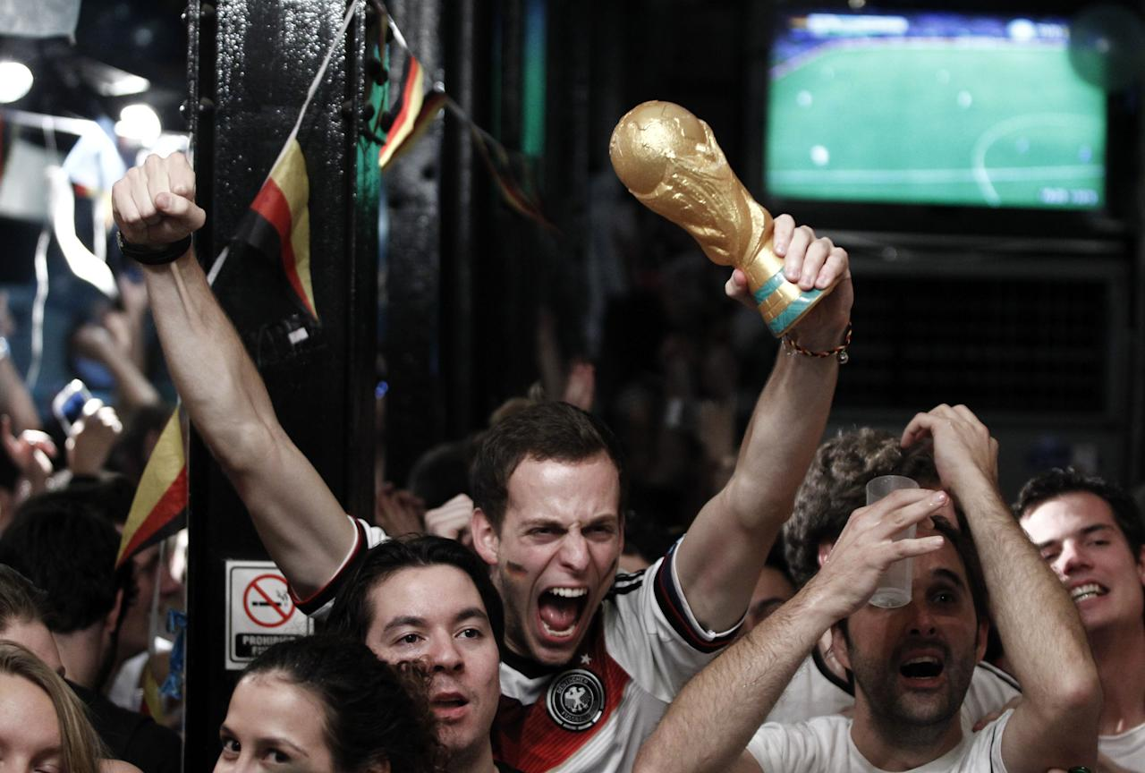 German fans celebrate after watching the FIFA World Cup Brazil 2014 final match between Germany and Argentina at a pizzeria in Buenos Aires on July 13, 2014 (AFP Photo/Emiliano Lasalvia)
