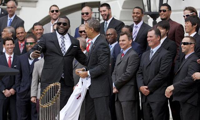 "Boston Red Sox designated hitter David ""Big Papi"" Ortiz, left, laughs, after taking a selfie with President Barack Obama, holding a Boston Red Sox jersey presented to the president, Tuesday, April 1, 2014, during a ceremony on the South Lawn of the White House in Washington where the president honored the 2013 World Series baseball champion Boston Red Sox. (AP Photo/Manuel Balce Ceneta)"
