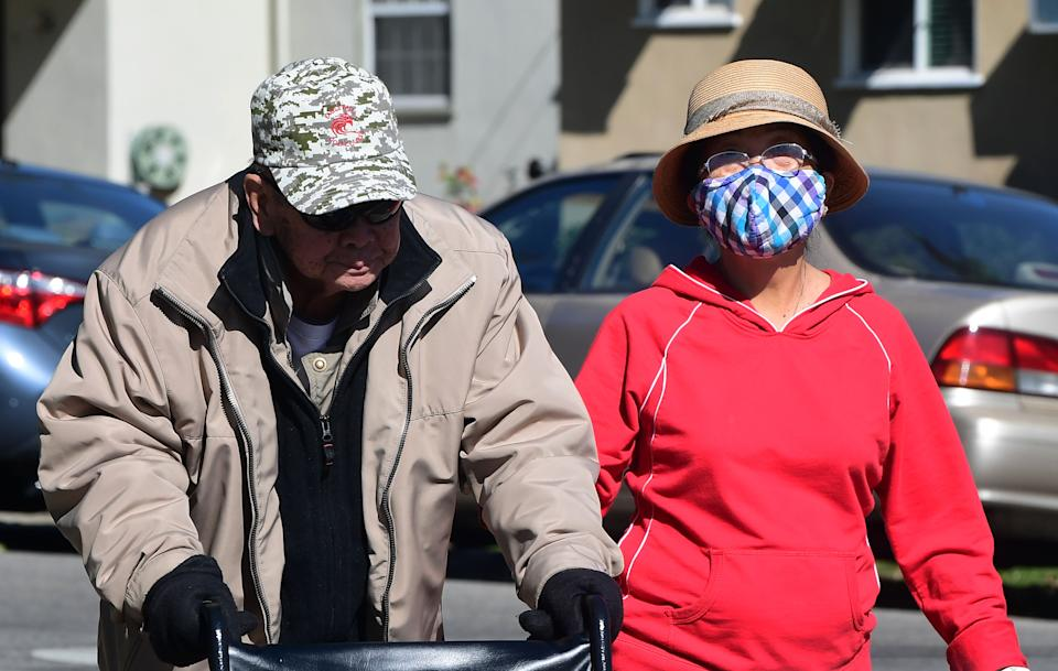 A woman wears a face mask as an elderly couple walk on a street in Alhambra, California on February 4, 2020. - As the coronavirus outbreak  spreads, fueling rumors and misinformation, a petition to cancel all classes in one US school district for fear of the virus has garnered nearly 14,000 signatures. The online petition posted on Change.org urges the Alhambra Unified School District located east of Los Angeles and with a heavily Asian population, to basically shut down until the outbreak is over. School district officials, however, have dismissed the petition as a bid to whip up hysteria over the deadly outbreak that has killed hundreds in China. (Photo by Frederic J. BROWN / AFP) (Photo by FREDERIC J. BROWN/AFP via Getty Images)