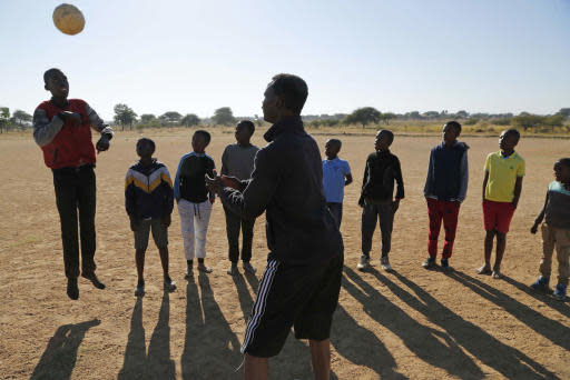 Double amputee and soccer coach, Tebogo Mofokeng, front, tosses a ball to his players during a training exercise in Winterveldt, South Africa, Sunday, June 17, 2018. Mofokeng's legs were amputated when he was a toddler but that didn't stop him fulfilling his dream of coaching young children. (AP Photo/Denis Farrell)