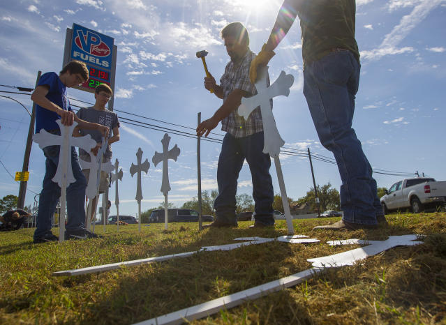 """<p>Doug John, of La Vernia, Texas, hammers in crosses at the VP Racing Fuels gas station just down the road from the First Baptist Church of Sutherland Springs, Monday, Nov. 6, 2017, in Sutherland Springs, Texas. John made the crosses last night with apprentices in a sheet metal workers Local 67 apprenticeship program. """"If it can happen in Sutherland Springs, Texas, it can happen anywhere,"""" said John of the mass shooting on Sunday at the church. (Photo: Mark Mulligan/Houston Chronicle via AP) </p>"""