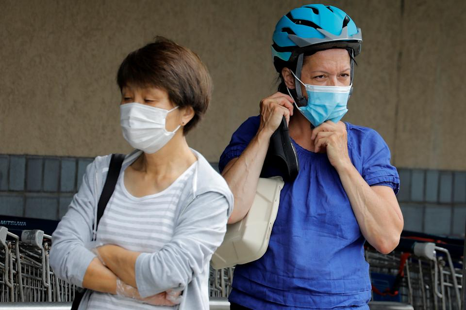 People wear protective face masks outside at a shopping plaza after New Jersey Governor Phil Murphy said he would sign an executive order requiring people to wear face coverings outdoors to prevent a resurgence of the coronavirus disease (COVID-19) in Edgewater, New Jersey, U.S., July 8, 2020. REUTERS/Mike Sega