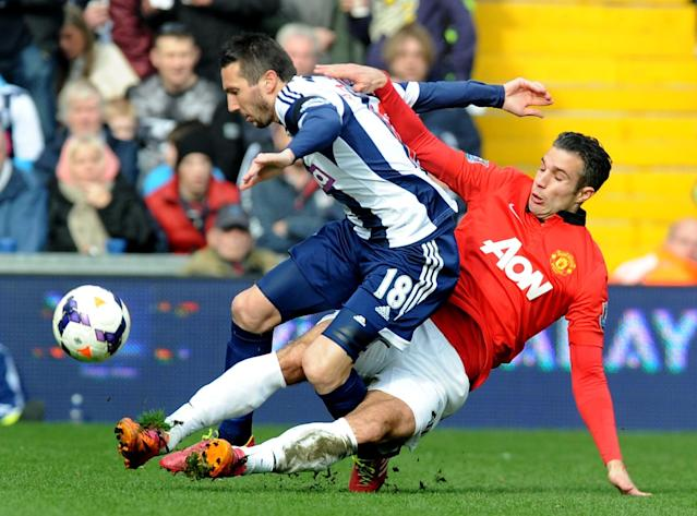 Manchester United's Robin van Persie tackles West Brom's Morgan Amalfitano during the English Premier League soccer match between West Bromwich Albion and Manchester United at The Hawthorns Stadium in West Bromwich, England, Saturday, March 8, 2014. (AP Photo/Rui Vieira)