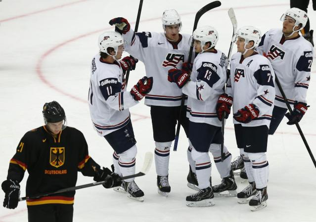 U.S. team players celebrate scoring past Germany's Dominik Kahun (L) during the first period of their IIHF World Junior Championship ice hockey game in Malmo, Sweden, December 29, 2013. REUTERS/Alexander Demianchuk (SWEDEN - Tags: SPORT ICE HOCKEY)