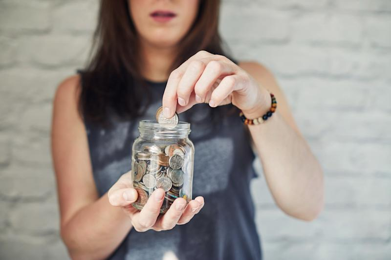 Young woman putting money into a jar