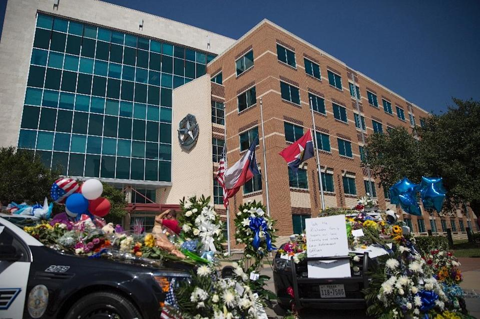 Two squad cars parked outside the Dallas Police Headquarters serve as memorials for victims of the sniper shooting on July 8, 2016 (AFP Photo/Laura Buckman)