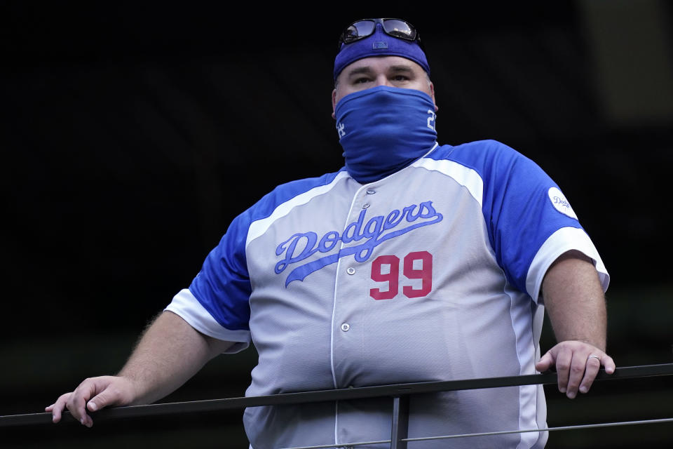 A Los Angeles Dodgers fan watches batting practice before Game 1 of the baseball World Series against the Tampa Bay Rays Tuesday, Oct. 20, 2020, in Arlington, Texas. (AP Photo/Eric Gay)