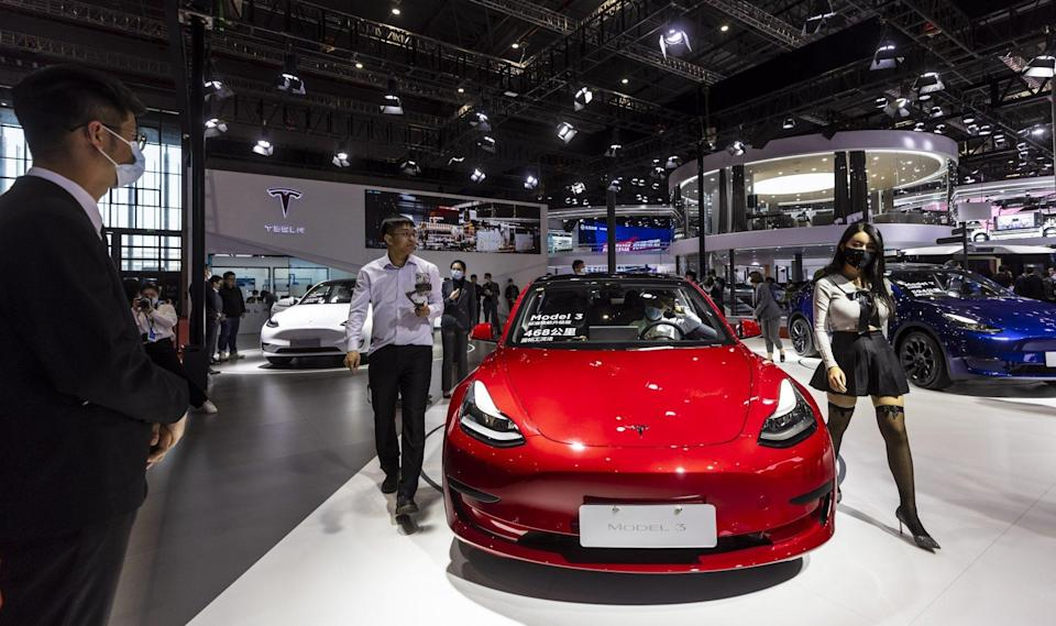 People walk by the Tesla Model 3 car at the Auto Shanghai 2021 motor show in Shanghai, China, 19 April 2021. Photo: EPA-EFE