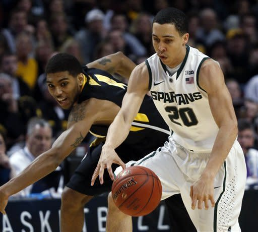 Iowa's Roy Devyn Marble and Michigan State's Travis Trice (20) go after a loose ball during the second half of an NCAA college basketball game at the Big Ten tournament Friday, March 15, 2013, in Chicago. (AP Photo/Charles Rex Arbogast)