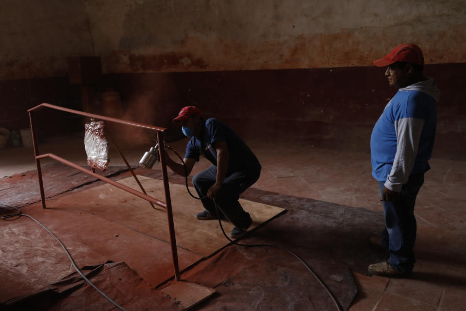 "A worker sprays primer onto a railing inside the former San Juan Bautista Convent, where restoration work is underway following damage in a 2017 earthquake, in Tlayacapan, Morelos state, Mexico, Tuesday, Oct. 13, 2020. ""Imagine, these structures sometimes took as long as 100 years to be built ... and in three years, we have managed to consolidate the structure,"" said architect Fernando Duarte Soriano, who is restoring churches for the Institute, known as the INAH, in Morelos state. (AP Photo/Rebecca Blackwell)"
