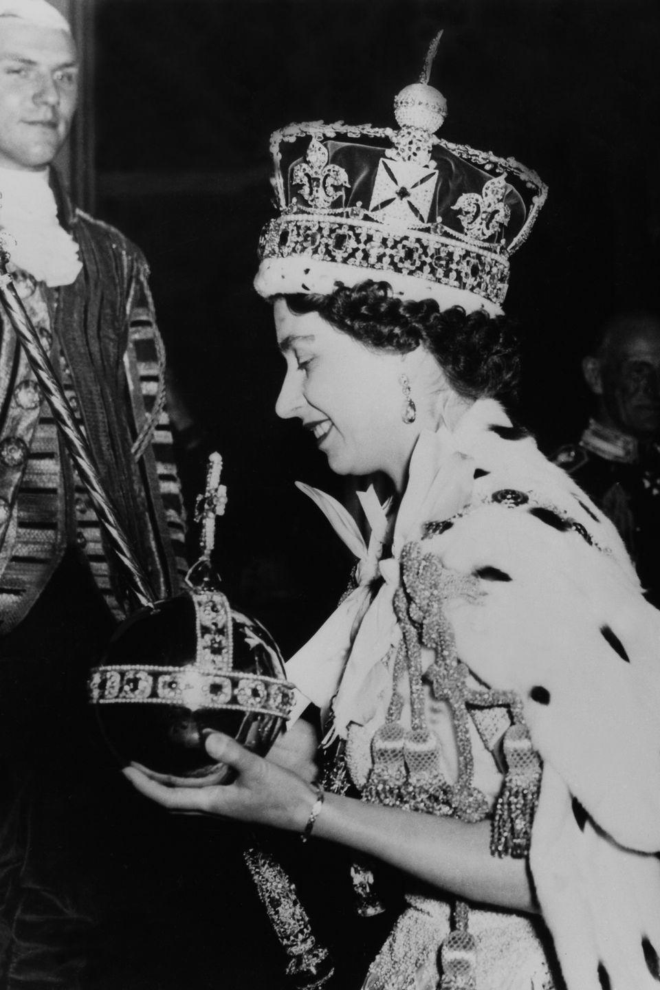 <p>She carried a large orb with a cross at the top while wearing a gigantic crown and a cape with tassels.</p>